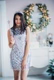 有不可思议的鞭子的性感的圣诞老人帮手女孩 穿在圣诞节背景的俏丽的妇女神仙美丽的发光的礼服 图库摄影