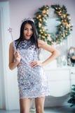 有不可思议的鞭子的性感的圣诞老人帮手女孩 穿在圣诞节背景的俏丽的妇女神仙美丽的发光的礼服 免版税库存照片