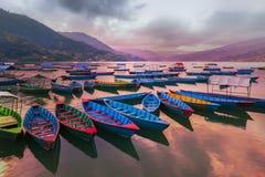有不同颜色的小船,天空蔚蓝反射在水中 从Phewa湖的看法 免版税库存照片