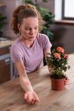 有不幸的卷曲的妇女在植物的过敏反应 免版税库存图片