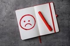 有不快乐的面孔和红色标志图画的笔记本在灰色背景,顶视图 免版税库存图片