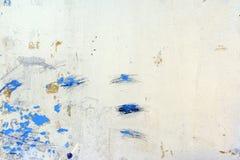 有不能理解的抓痕、污点和离婚的墙壁 与蓝色油漆斑点的异常的白色背景  免版税库存照片