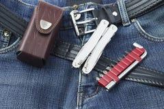 有不锈的multitool刀子和套的蓝色牛仔裤螺丝刀 免版税图库摄影