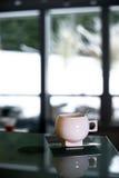 有不锈钢匙子和茶碟的典雅的瓷杯子 库存图片