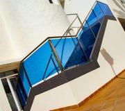 有不锈钢栏杆的现代石台阶与蓝色玻璃 免版税库存图片