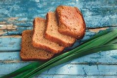有与大蒜,农村自然食物绿色新鲜的叶子的家制面包在葡萄酒老Panited木板的,烘烤 顶层 图库摄影