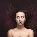 有专业显示大圆环的构成和发型的美丽的深色的妇女在嘴和耳环 登广告者做广告 飞行灰色头发夫人年轻人的有吸引力的背景梳子 库存图片