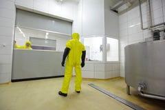有专家的工作者在restriced通入工业areahigh压力洗衣机清洁地板的制服的 免版税库存图片