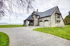 有专栏门廊和车库的惊人的石房子 免版税库存照片