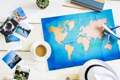 有世界和照片被折叠的纸地图的旅行家书桌  图库摄影