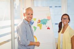 有世界地图的愉快的商人在会议室 免版税库存照片