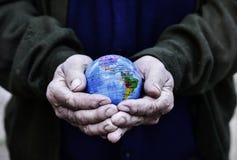 有世界地球的老人在他的手上 免版税图库摄影