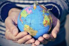 有世界地球的年轻人作为圣诞节球在他的手上 免版税库存照片