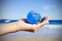 有世界地球的年轻人在他的手上, vignetted 库存图片