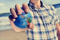 有世界地球的年轻人在他的手上 库存图片