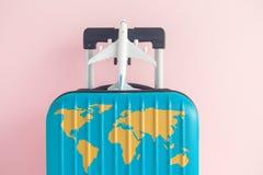 有世界大陆的蓝色行李映射和在柔和的淡色彩玫瑰背景的飞机玩具 免版税库存图片