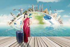 有世界纪念碑手提箱和地图的印地安妇女  免版税图库摄影