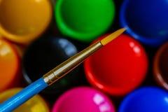 有丙烯酸酯或油漆的在五颜六色的艺术家的调色板,选择聚焦的管和刷子 免版税库存照片