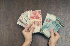 有东南亚金钱的女性手  香港,印度尼西亚,马来西亚,泰国,新加坡货币  旅行,开户概念 免版税库存照片