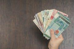 有东南亚金钱的女性手  香港,印度尼西亚,马来西亚,泰国,货币新加坡元 汽车城市概念都伯林映射小的旅行 免版税库存图片