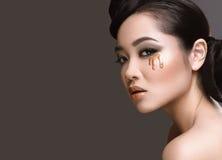 有东方类型的晚上头发和构成美丽的女孩与下落在她的面孔 秀丽表面 免版税库存图片