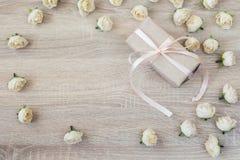 有丝带和桃子玫瑰的礼物盒在与emp的木背景 免版税库存照片