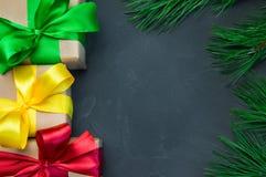 有丝带弓的礼物盒和分支在黑暗的具体背景的圣诞树 库存图片