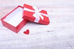 有丝带弓的红色礼物盒在葡萄酒白色木桌上打开了 库存照片
