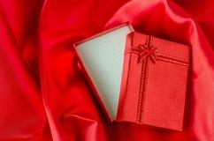 有丝带弓的被打开的红色礼物盒在红色缎纺织品 免版税库存图片