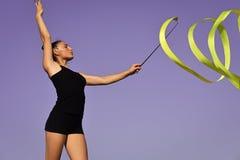 有丝带的体操运动员 妇女体操运动员漩涡在蓝天背景的绿色丝带 库存照片