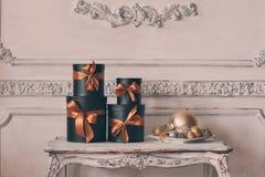 有丝带的被包裹的礼物黑匣子,在桌豪华白色墙壁上的圣诞节礼物设计浅浮雕灰泥 免版税图库摄影