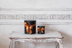 有丝带的被包裹的礼物黑匣子,在桌豪华白色墙壁上的圣诞节礼物设计浅浮雕灰泥 图库摄影