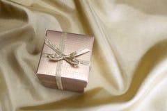 有丝带的金黄箱子在金黄丝绸 免版税库存图片