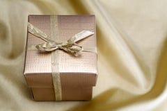 有丝带的金黄箱子在金黄丝绸 库存照片