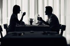 有两个偶然年轻的成人在膳食的一次交谈 正式提案,谈话在餐馆 尝试的食物,提议,特别菜单 库存照片