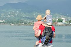 有两个儿子的父亲在海滩站立 回到视图 免版税库存图片