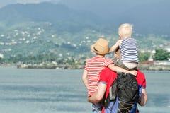 有两个儿子的父亲在海滩站立 回到视图 免版税库存照片