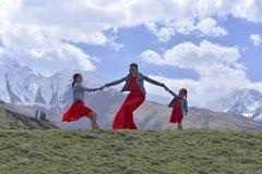 有两个女儿的一年轻女人休息在积雪覆盖的山的红色礼服的在春天 免版税库存照片