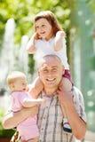 有两个女儿的愉快的父亲在晴天 免版税库存图片