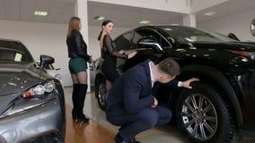 有两个女孩的一个年轻成功的人在陈列室里选择一辆新的汽车 股票视频