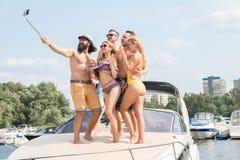 有两个女孩的三个年轻人做在游艇的selfie 免版税库存照片