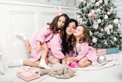 有两个女孩的少妇在礼物和玩具中的圣诞树附近 库存图片