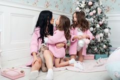 有两个女孩的少妇在礼物和玩具中的圣诞树附近 图库摄影