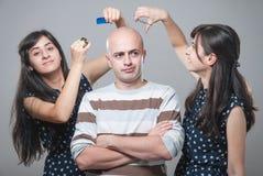 有两个女孩的恼怒的秃头人 免版税图库摄影