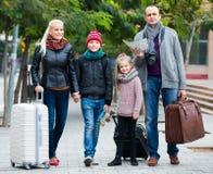 有两个孩子的与地图的父母和行李 免版税库存照片