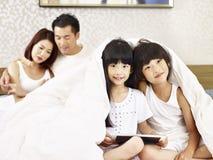 有两个孩子的亚洲家庭获得乐趣在卧室 免版税库存照片