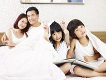 有两个孩子的亚洲家庭获得乐趣在卧室 免版税图库摄影