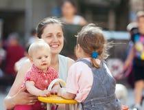 有两个孩子的妇女在城市操场 免版税库存图片