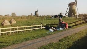 有两个孩子的妈妈坐草在绕环投球法附近 在夏天日落牧人风景的平安的家庭统一性 4K 股票视频