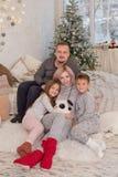 有两个孩子的家庭在圣诞树下 免版税库存图片
